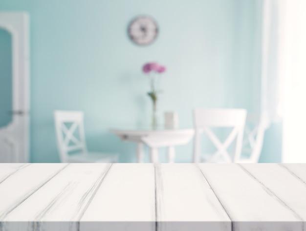 Escritorio blanco frente a la mesa de comedor borrosa contra la pared Foto gratis