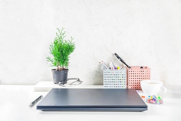 Escritorio creativo de oficina con suministros y taza de café. mesa de oficina blanca con laptop, teclado, cuaderno en blanco, gafas, suministros y taza de café. vista superior del espacio de copia de diseño flatlay Foto Premium