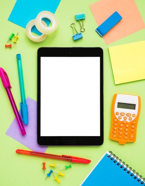 Escritorio desordenado con tableta en blanco Foto gratis