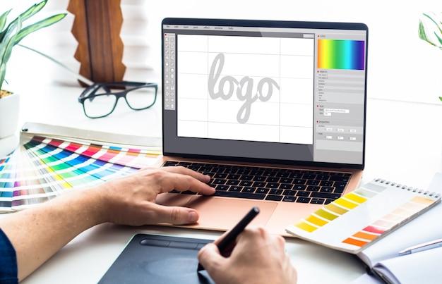 Escritorio de diseño gráfico con laptop y herramientas. Foto Premium