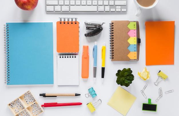 Escritorio de espacio de trabajo creativo en blanco con coloridos suministros de oficina. Foto gratis