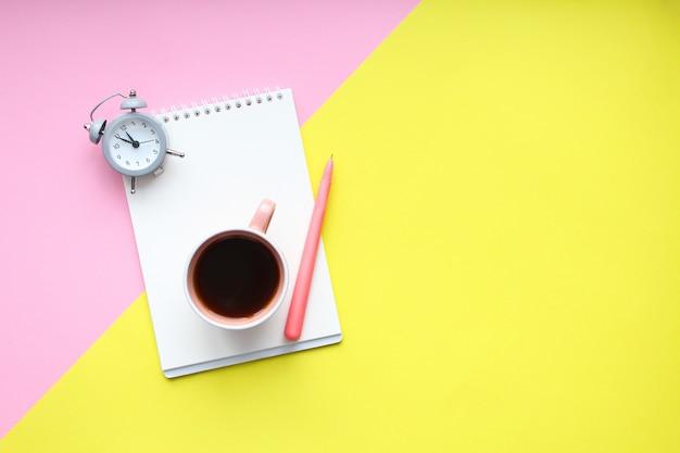 Escritorio para estudiantes con útiles, cuaderno, taza de café, bolígrafo, mini reloj despertador. Foto Premium