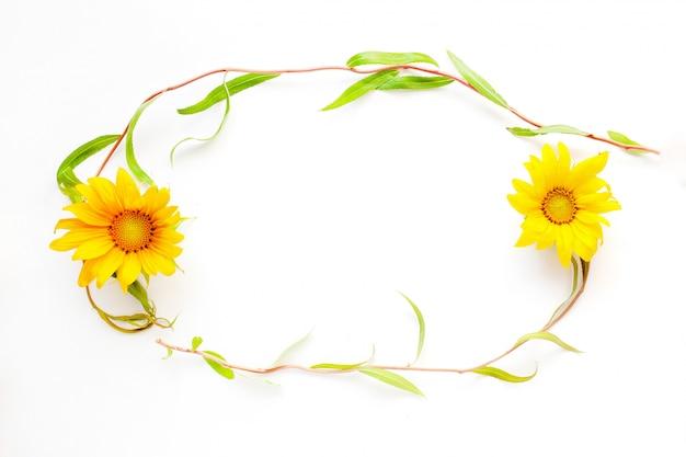 Escritorio de girasol, marco de belleza de verano de ramitas y flores sobre un fondo blanco close-up Foto Premium
