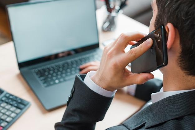 Escritorio de oficina con ordenador portátil y hombre de negocios Foto gratis