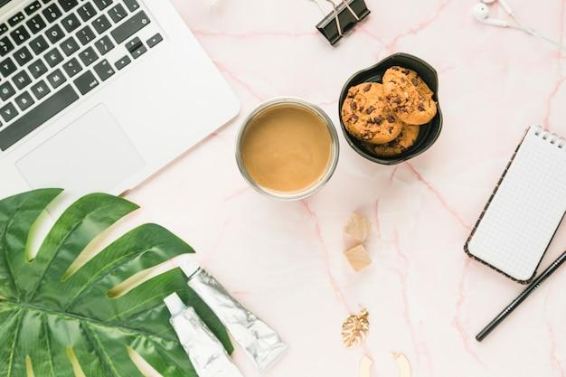 Escritorio de oficina con una taza de café y galletas Foto gratis