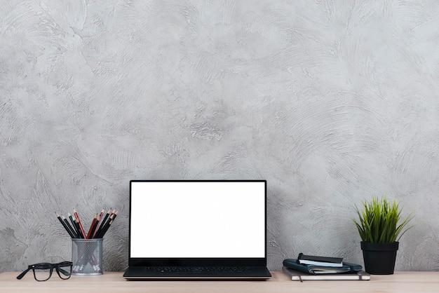 Escritorio con ordenador portátil y elementos de oficina Foto gratis
