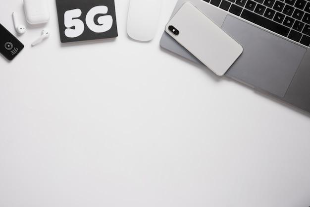 Escritorio plano con teléfono en la computadora portátil y texto de 5 g Foto gratis