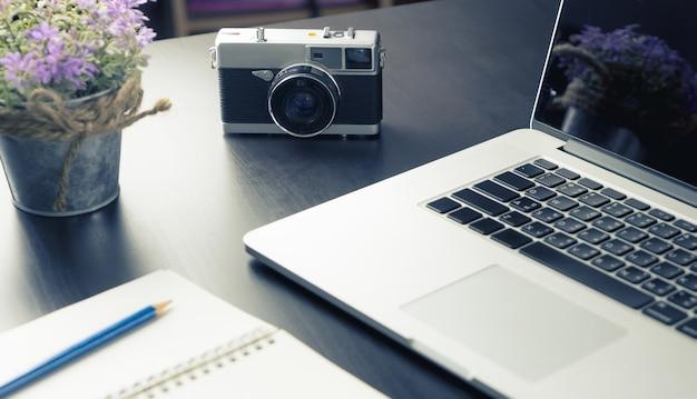 Escritorio de trabajo creativo con notebook y cámara vintage. Foto Premium