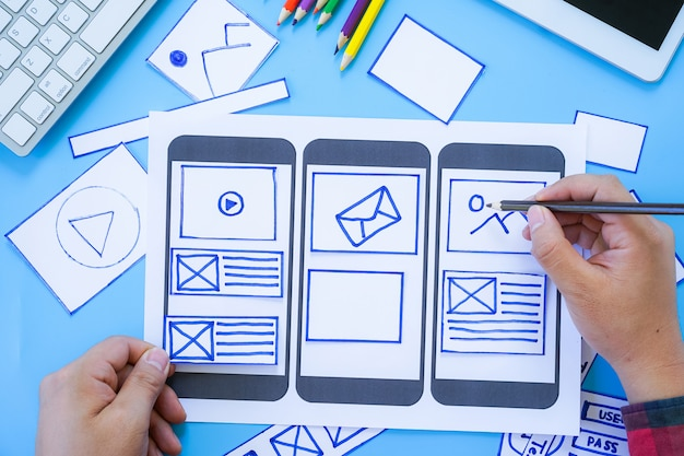 Escritorio de trabajo con manos que dibujan pantallas para el desarrollo de sitios web adaptados a dispositivos móviles con ui / ux Foto Premium