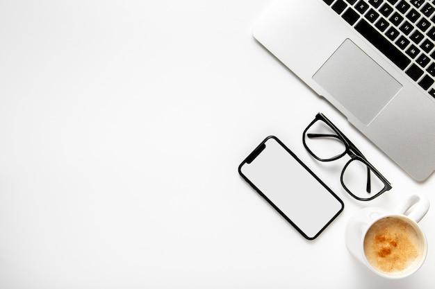 Escritorio de vista superior con computadora portátil y teléfono Foto gratis