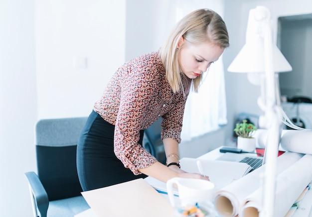 Escritura de la empresaria en fichero sobre el escritorio en oficina Foto gratis