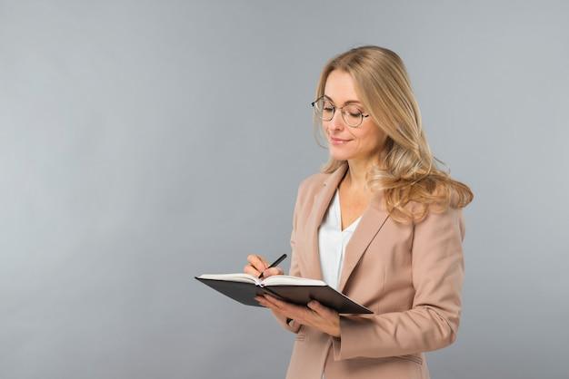 Escritura joven sonriente de la empresaria en el diario con la pluma contra fondo gris Foto gratis