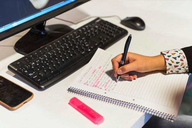 Escritura de la mano de cultivo en el cuaderno cerca de la computadora Foto gratis