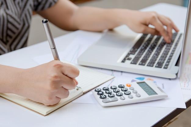 La escritura de la mujer hace la nota y usando la oficina de las finanzas del ordenador portátil en casa. Foto Premium