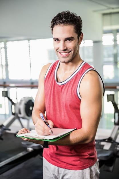 Escritura sonriente del hombre en el tablero en el gimnasio Foto Premium