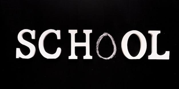 Escuela de inscripción sobre fondo negro. Foto gratis