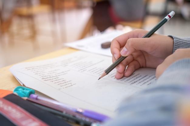 Escuela / universidad manos de estudiantes que toman exámenes, escribiendo sala de examen con lápiz de sujeción Foto Premium