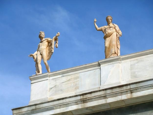 Esculturas de mármol del dios griego y la diosa contra el cielo azul, edificio histórico en atenas, grecia Foto Premium