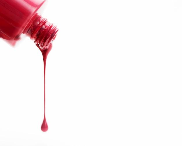 Esmalte de uñas brillante rojo que vierte en el fondo blanco Foto gratis