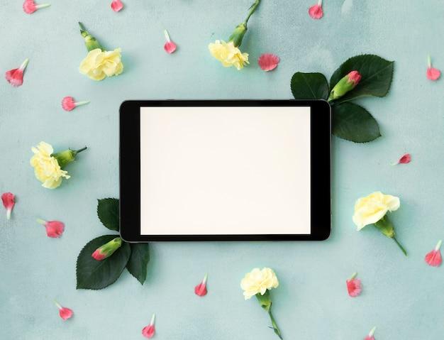 Espacio de copia horizontal tableta digital rodeado de flores Foto gratis