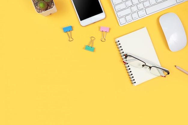 Espacio de trabajo con computadora portátil y suministros de oficina en amarillo Foto Premium