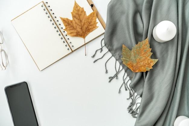 Espacio de trabajo de escritorio de oficina en casa con teléfono móvil con pantalla negra en blanco, cuaderno, hojas de arce, velas en blanco Foto Premium