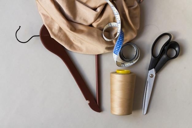 Espacio de trabajo de modista con herramientas y colgador. Foto gratis