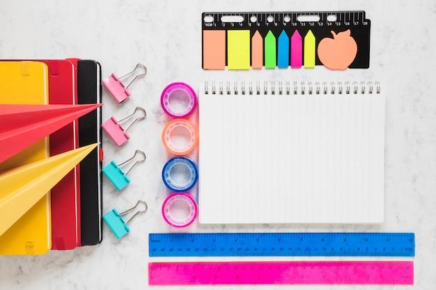 Espacio de trabajo organizado con cuaderno en blanco y suministros de oficina a su alrededor. Foto gratis