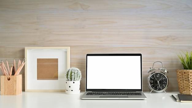 Espacio de trabajo portátil maqueta, marco de fotos, lápiz y cactus en el escritorio con pared de madera. Foto Premium