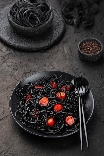 Espagueti negro en plato con tomates Foto gratis