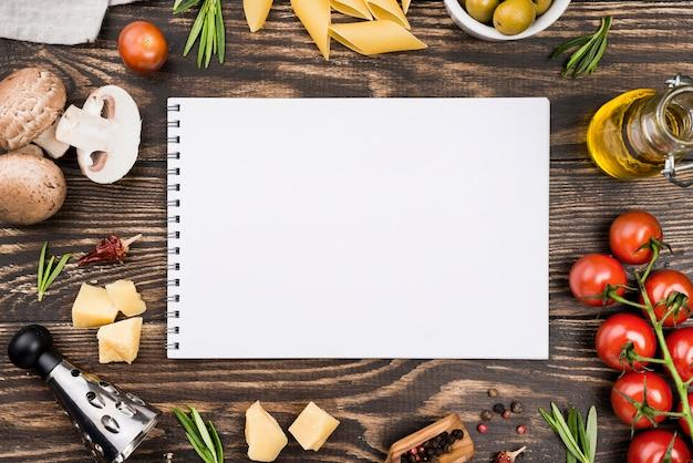 Espaguetis con aceitunas y verduras y cuaderno Foto gratis