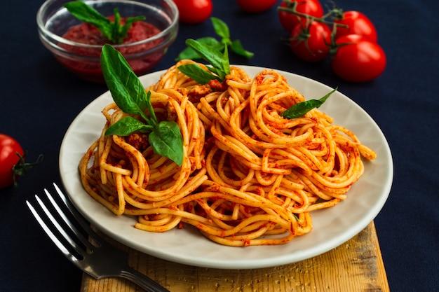 Espaguetis a la boloñesa en un plato en azul Foto Premium