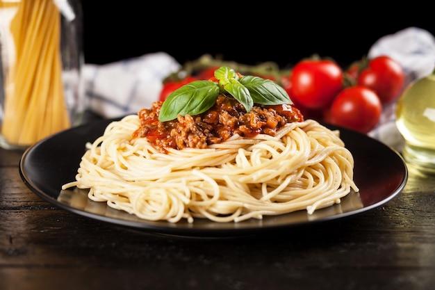 Espaguetis a la boloñesa sobre fondo oscuro Foto Premium