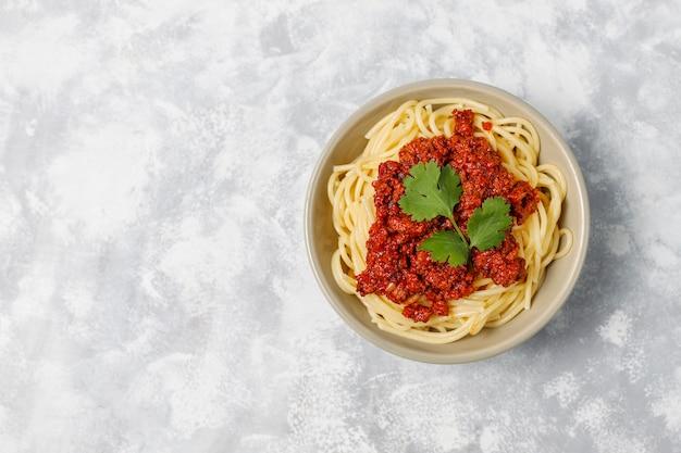 Espaguetis a la boloñesa sobre hormigón gris Foto gratis