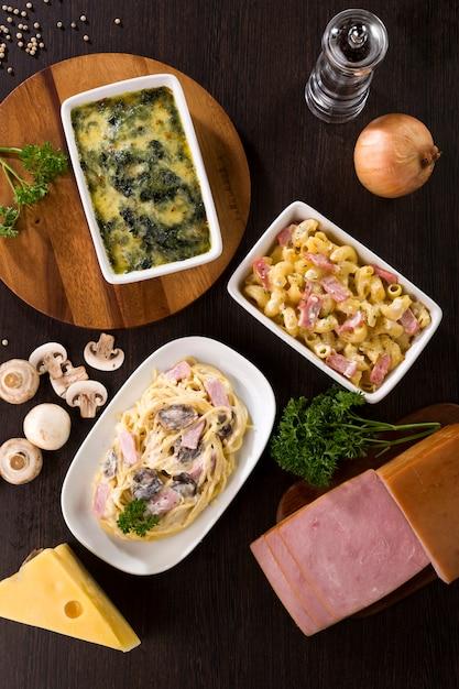 Espaguetis a la carbonara, jamón de macarrones con queso y espinacas al horno con queso Foto Premium