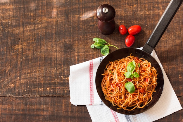 Espaguetis cocidos con albahaca y tomates en mesa de madera Foto gratis