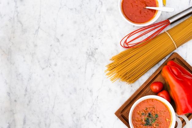Espaguetis crudos pasta y salsa con tomates frescos sobre fondo con textura de mármol Foto gratis