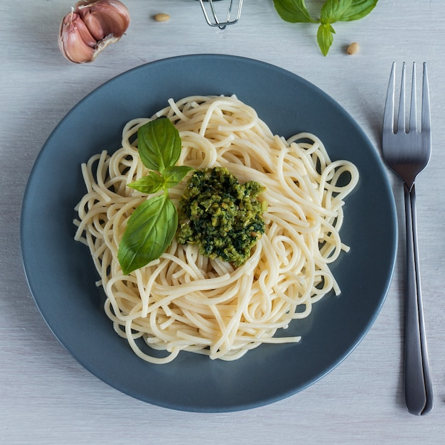 Espaguetis. espaguetis con salsa de pesto casera, aceite de oliva y hojas de albahaca. vista superior Foto Premium