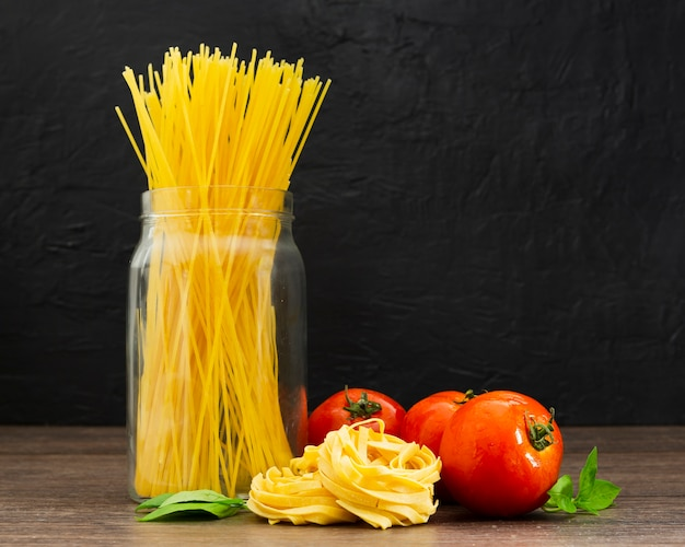 Espaguetis en frasco con tomates Foto gratis