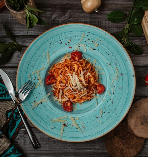 Espaguetis italianos en salsa de tomate con parmesano dentro de la placa azul, vista superior. Foto gratis
