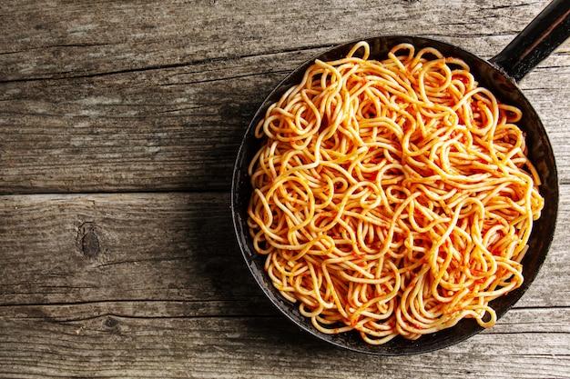 Espaguetis italianos con salsa de tomate en sartén Foto gratis
