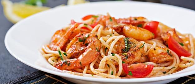 Espaguetis de pasta con camarones, tomate y perejil. comida saludable. comida italiana. Foto gratis