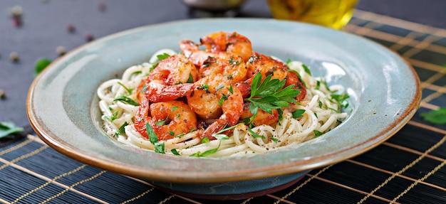 Espaguetis de pasta con camarones, tomate y perejil picado. comida sana. comida italiana Foto gratis