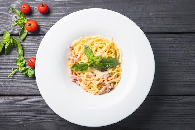 Espaguetis con queso y albahaca en un plato Foto gratis