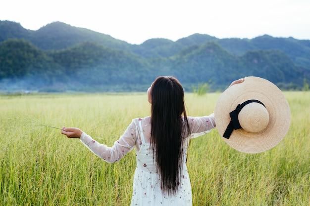 La espalda de una bella mujer que es feliz en el prado con una gran montaña como a. Foto gratis