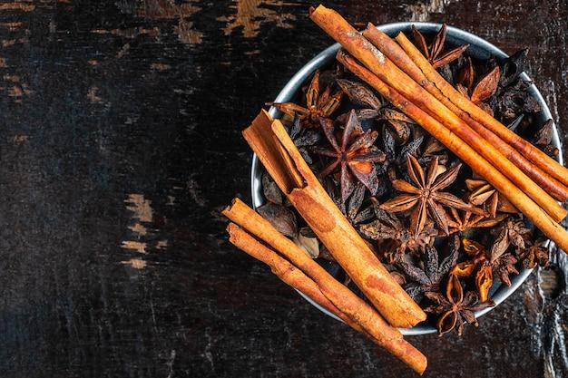 Especias de canela y estrellas de anís en un bol sobre la mesa Foto Premium