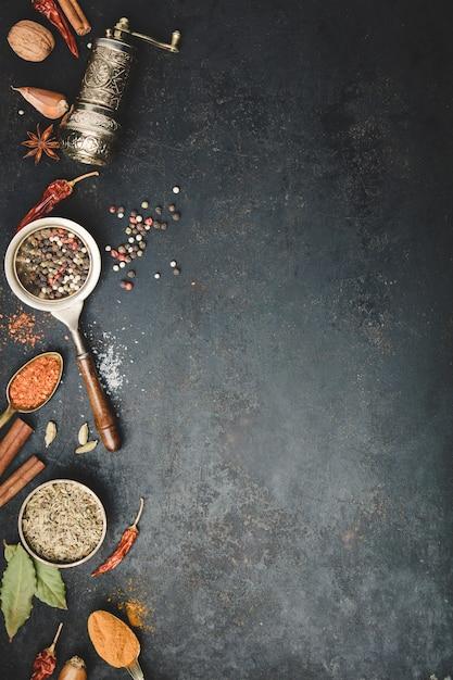 Especias y molinillo de pimienta vintage sobre fondo de hormigón negro Foto Premium