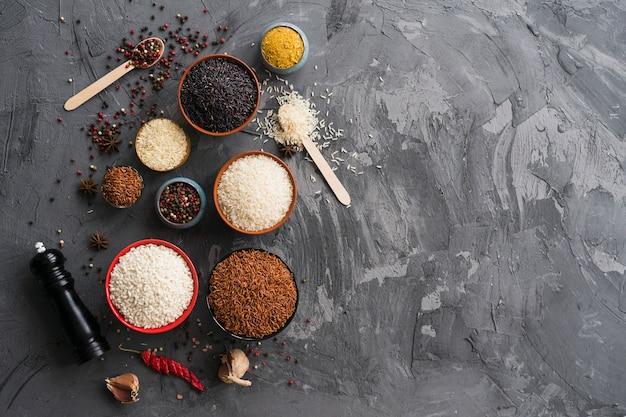 Especias secas con variedad de cuencos de arroz; ajo y peppermill en el fondo concreto texturizado Foto gratis