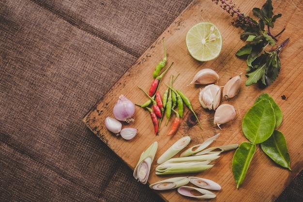 Especias tom yum que se colocan en una tabla de cortar de madera marrón y tienen una madera de color marrón oscuro. Foto gratis