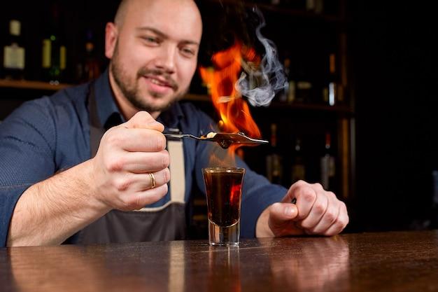 Espectáculo de fuego en el bar. el barman prepara un cóctel alcohólico caliente y enciende el bar. camarero prepara un cóctel ardiente. fuego en barra. Foto Premium